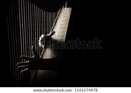 Harp player. Hands playing Irish harp strings. Music instrument closeup. Harpist with celtic harp #1161574978
