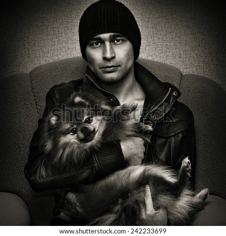 Harsh brutal man with Spitz dogs on their hands. Black and white photo in a dark style