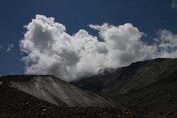 Harsh dark glaciers of the highlands of Kazakhstan under snow-white clouds on a summer day. Bleaching rocks paint the slopes of the glacier in dark colors.