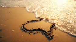 Hart shape drawn on beach sand is being washed by sea waves with sunset reflection