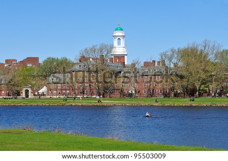 Harvard and the Charles. People jogging and walking along the riverbank in early spring.