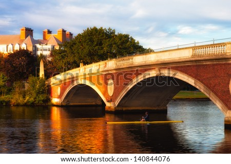 Harvard University bridge over the Charles River in early morning golden light, with a lone sculler passing under the span
