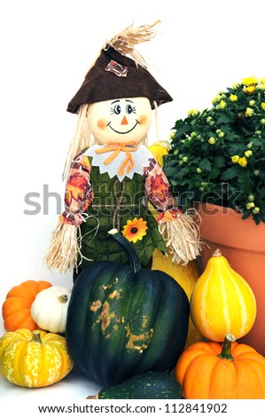 harvest and halloween decoration with squash, pumpkin, and scarecrow