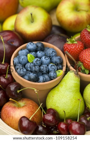harvest of summer or autumn fresh fruit including: blueberries, strawberries, apples, cherries and pears