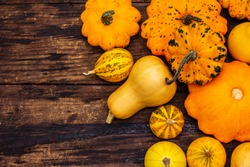 Harvest of various ripe pumpkins. Colorful festive background, Thanksgiving or Halloween Day. Old wooden boards background, top view