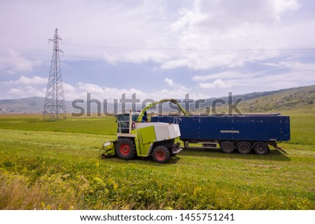 harvest time - combine machine loading harvested grain into the bunker of the truck #1455751241