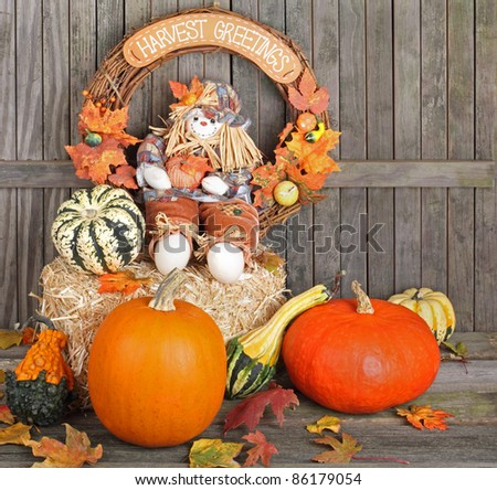 Harvest wreath and doll on a straw bale with pumpkins and gourds