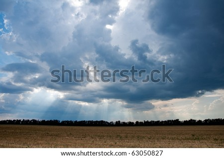 Harvested field, a beautiful stormy sky. Sunbeams.