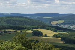 harvested field with warped bales of straw besides forest in Eifel from high angle, Germany, Gerolstein