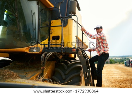 Harvester machine driver climbing into a cab to harvest his wheat field. Farmer getting in combine on ladder holding railing. Agronomist looking at camera. Rancher after harvesting work.