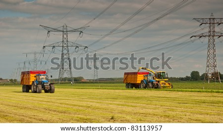 Harvesting dried grass between power pylons in the Netherlands