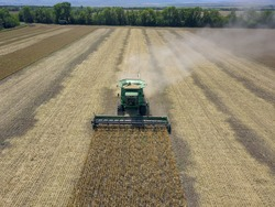 Harvesting of wheat in summer. Harvesters working in the field. Combine harvester agricultural machine collecting golden ripe wheat on the field. View from above. View from drone.