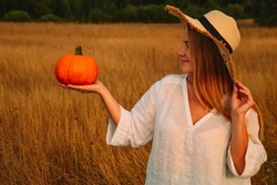 Harvesting pumpkins. A young woman in a white shirt and a straw hat holds an orange pumpkin against the background of an autumn field. Preparing for Halloween. Warm cozy autumn in the countryside
