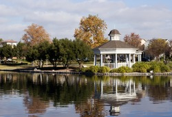 Harveston Lake Park in Temecula California. A white gazebo that is near a large body of water. Trees are placed in surrounding areas. Cloudy blue sky, and ripples on the lake.