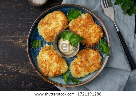 Hashbrown, hash brown potatoes fried pancakes, traditional american cuisine. Crispy hashed browned potatoes in blue plate on dark brown table, top view. Stock photo ©