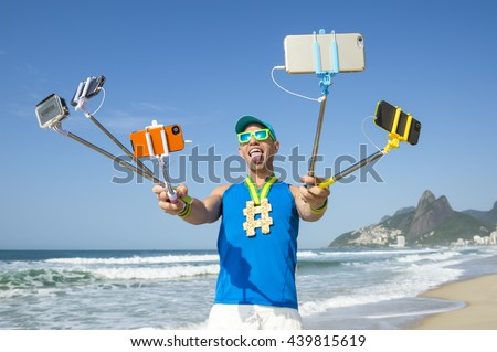 Hashtag gold medal athlete posing for a picture with mobile phones on selfie sticks on Ipanema Beach in Rio de Janeiro, Brazil