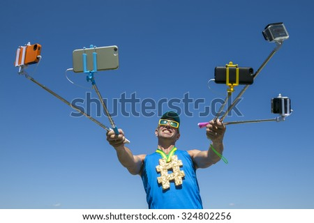 Hashtag gold medal athlete smiling for his many gadgets on selfie sticks as he poses for a picture