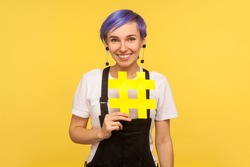 Hashtag, internet popularity. Portrait of cheerful stylish hipster girl with violet short hair in denim overalls holding big yellow hash sign and smiling. isolated on yellow background, studio shot
