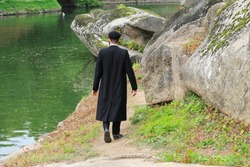 Hasidic Jew boy in black traditional clothing walk in the park in Uman, Ukraine, the time of the Jewish New Year,  Religious Jew, Orthodox,  follower of Judaism