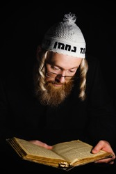 Hasidic jew reading Torah. Religious orthodox jew with sidelocks and red beard in white bale praying in the dark. Low key photo. Vertical orientation