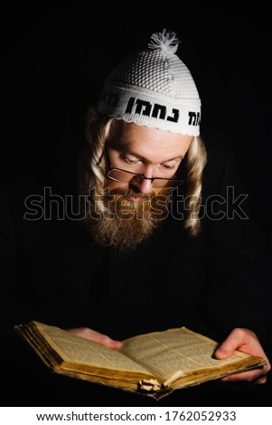 Hasidic jew reading Torah. Religious orthodox jew with sidelocks and red beard in white crocheted bale praying in the dark. Low key photo. Vertical orientation Foto stock ©