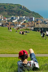 Hastings,East Sussex/UK 07/05/18 A beautiful May Day bank holiday Monday. A young lad relaxes on the West Hill with views of the Old Town and East Hill with its funicular railway in the distance