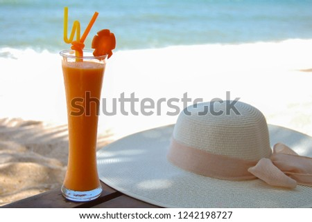 Hat and orange juice with slice carrot in cocktail glass and on the beach. Summer holiday concept #1242198727
