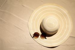 Hat and sunglasses on sand, top view. Beach accessories