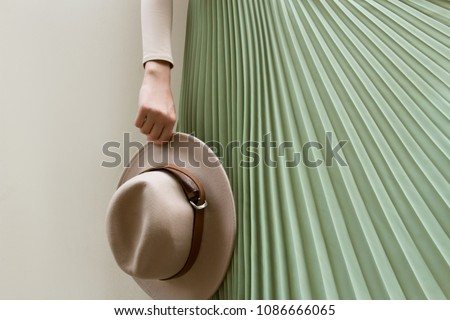 Hat, beige blouse and turqoise pleats skirt on light street backgraund.  Fashion and stylish concept. ストックフォト ©