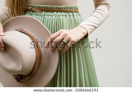 Hat, beige blouse and turqoise pleats skirt on light street backgraund.  Fashion and stylish concept. - Shutterstock ID 1086666191
