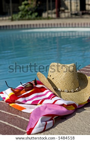 Hat, glasses and a beach towel by a pool