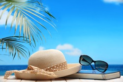 Hat,glasses and book on beach table,Beach concept.