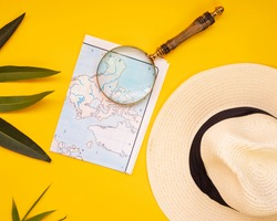 hat map and magnifying glass on yellow background, travel concept