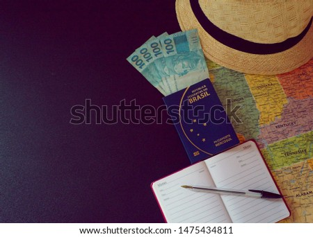 Hat, map, brazilian passport, brazilian money, brazilian currency, notepad and pen on black table with empty place for text.