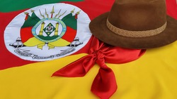 Hat, red gaucho scarf and State Flag of Rio Grande do Sul - Brazil, on the table. Decoration to commemorate the traditional Week in southern Brazil. Farroupilha from the Gauchos.