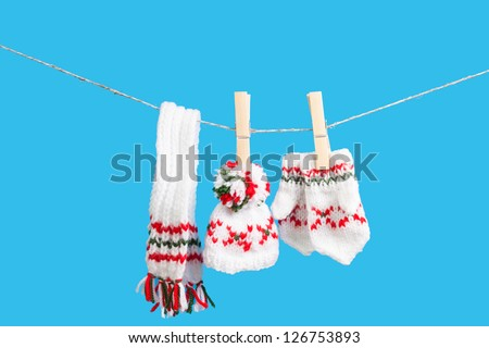 hat, scarf and pair of gloves drying in the open air hanging on clothes line affixed with wooden pegs