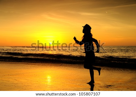 Hat woman running on the beach at sunset