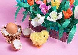 Hatched toy easter chick, hatch egg and spring tulip flowers on pink background. Copyspace
