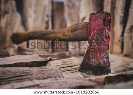 Hatchet axe being stuck in a pile of split wood logs used for fire. Concept of making logs with natural colors- Axe viewed from the front and side.