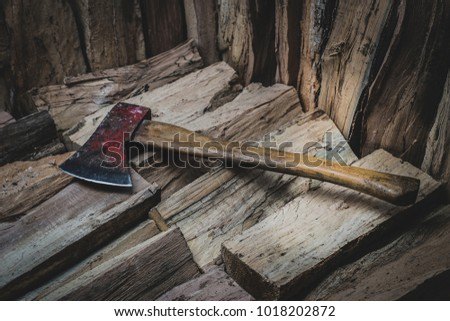 Hatchet axe lying on a pile of split wood logs used for fire. Concept of making logs portrayed in natural colors- Axe viewed from the top side with a shiny sharp blade.