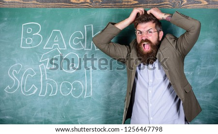 Hate school. Teacher or educator stands near chalkboard with inscription back to school. Teacher unhappy shouting hysterically face. Teacher goes mad about schooling. Man refuses begin work at school.