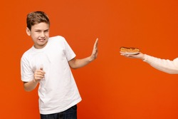 Hate sweets. Teen boy feeling disgust, refusing chocolate donut, orange background