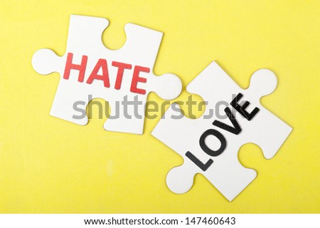 Hate versus love concept words on two pieces of jigsaw puzzle