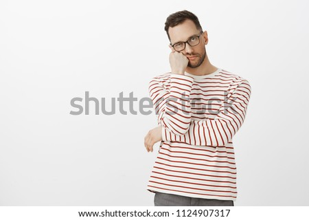 Hate waiting in queues. Portrait of annoyed tired handsome guy with bristle in black eyewear, leaning face on hand and looking indifferent at camera, standing bored over gray background