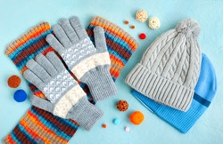 Hats, gloves and a scarf on a textured background. Warm clothes for autumn and winter in the form of hats, gloves and a scarf. Fashionable set of clothes made of hats and gloves.