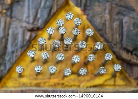 Hats of nails hammered into a wooden yellow pyramid. Freemasonry and its signs. Secret symbols of Freemasons. Macro. Shallow depth of field. Daylight
