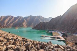 Hatta dam during the day with boats docked on the pier and mountains around in rocky regious on outskirts of Dubai