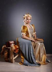 Haughty queen in royal dress reading a book  isolated on grey