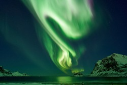 HAUKLANDBEACH, LOFOTEN / NORWAY– MARCH 07, 2019: A view to the fjord at Hauklandbeach (near to village Leknes / Lofoten). huge northern lights is shining/glowing over a island with starry stars.