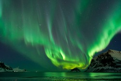 Hauklandbeach, Lofoten / Norway - March 7th 2019: A view to the fjord at Hauklandbeach (near village Leknes). huge nothern lights / aurora is shining / glowing over an island with starry stars